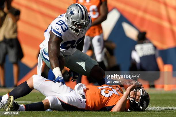 Trevor Siemian of the Denver Broncos is touched by Benson Mayowa of the Dallas Cowboys after tripping in the backfield during the second quarter on...