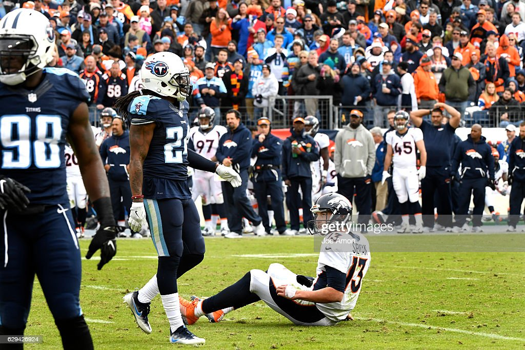 Trevor Siemian #13 of the Denver Broncos looks up at Daimion Stafford #24 of the Tennessee Titans after a push that slid him through the backfield at Nissan Stadium, Nashville, TN December 11, 2016.