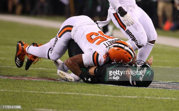 Trevor Siemian of the New York Jets is hurt on this play after he is tackled after a pass by Myles Garrett of the Cleveland Browns during their game...