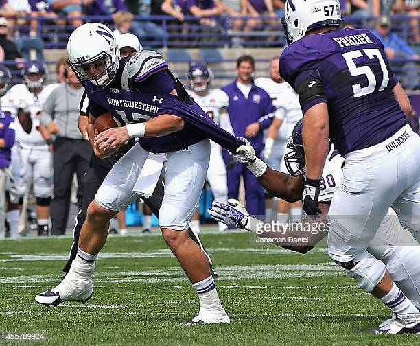 Trevor Siemian of the Northwestern Wildcats is sacked by JeanMarc Charles of the Western Illinois Leathernecks on September 20 2014 at Ryan Field in...
