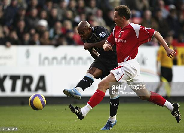 Trevor Sinclair of Man City shoots as he is challenged by Matt Holland of Charlton during the premiership match between Charlton Athletic and...
