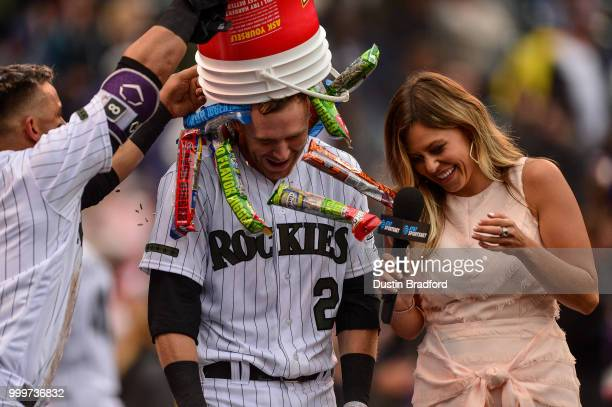 Trevor Story and Gerardo Parra of the Colorado Rockies celebrate a ninthinning walkoff home run by Story over the Seattle Mariners as he gives a TV...