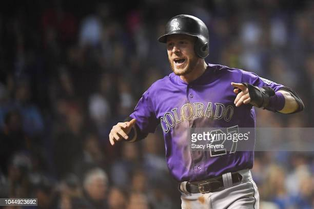 Trevor Story of the Colorado Rockies celebrates after scoring a run in the thirteenth inning to give the Rockies a 2-1 lead against the Chicago Cubs...