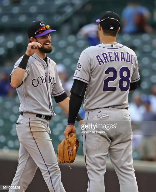 Trevor Story of the Colorado Rockies congratulates Nolan Arenado after a win against the Chicago Cubs at Wrigley Field on May 2 2018 in Chicago...