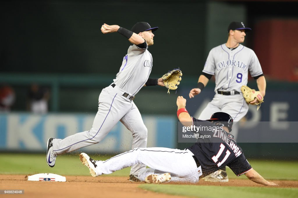 Trevor Story #27 of the Colorado Rockies forces out Ryan Zimmerman #11 of the Washington Nationals on a ground ball double play hit by Howie Kendrick #12 (not pictured) in the eight inning during a baseball game at Nationals Park on April 12, 2018 in Washington, DC.