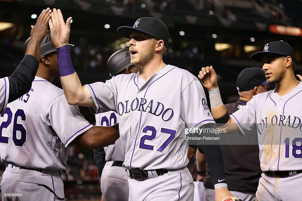 Trevor Story #27 of the Colorado Rockies high-fives teammates after defeating the Arizona Diamondbacks 10-5 in the MLB opening day game at Chase Field on April 4, 2016 in Phoenix, Arizona.