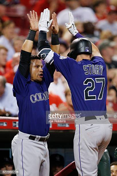 Trevor Story of the Colorado Rockies is congratulated by Gerardo Parra after hitting a solo home run against the Cincinnati Reds in the eighth inning...