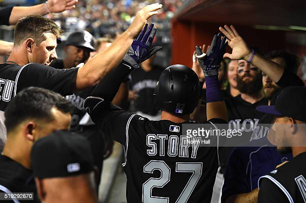 Trevor Story of the Colorado Rockies is congratulated by teammates in the dugout after hitting a fourth inning home run against the Arizona...