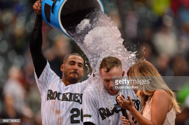 Trevor Story of the Colorado Rockies is doused with ice water by Ian Desmond as he gives a TV interview to Taylor McGregor after hitting a...