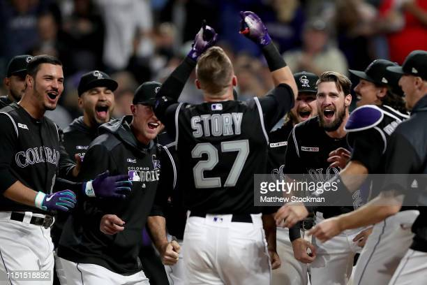 Trevor Story of the Colorado Rockies is met at the plate by his teammates after hitting a 2 RBI walk off home run in the ninth inning against the...