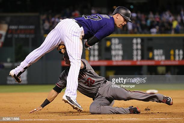 Trevor Story of the Colorado Rockies is tagged out by third baseman Jake Lamb of the Arizona Diamondbacks while trying to reach third on an RBI...