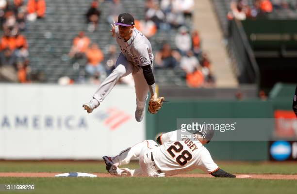 Trevor Story of the Colorado Rockies jumps over Buster Posey of the San Francisco Giants after Posey was forced out at second base in the fifth...
