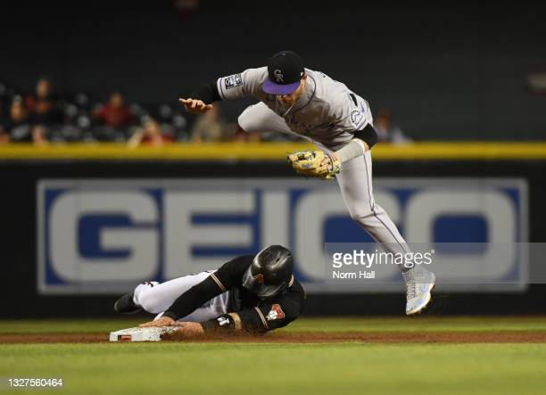 Trevor Story of the Colorado Rockies leaps over Christian Walker of the Arizona Diamondbacks after the force out at second base in the second inning...