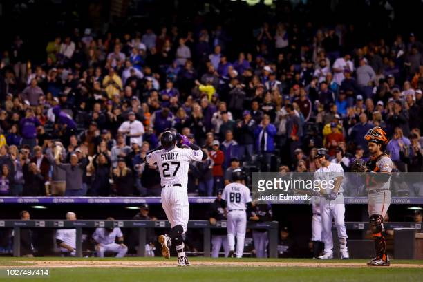 Trevor Story of the Colorado Rockies points to the sky to celebrate his home run during the fourth inning as catcher Aramis Garcia of the San...