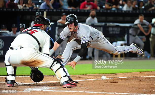 Trevor Story of the Colorado Rockies scores in the ninth inning against A J Pierzynski of the Atlanta Braves at Turner Field on July 16 2016 in...