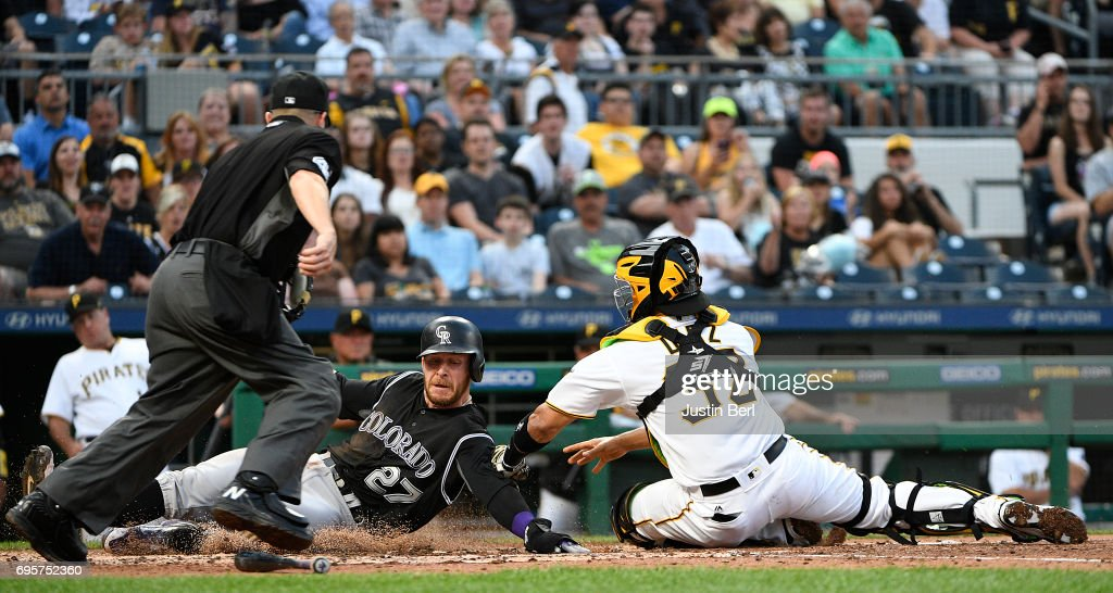 Trevor Story #27 of the Colorado Rockies slides safely past Elias Diaz #32 of the Pittsburgh Pirates to score on an RBI single by Tony Wolters #14 in the fifth inning during the game at PNC Park on June 13, 2017 in Pittsburgh, Pennsylvania.