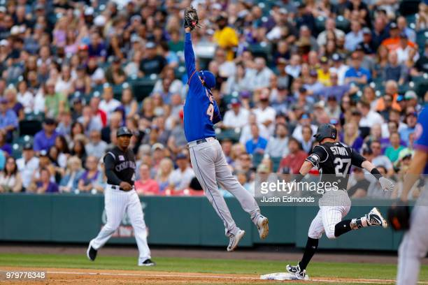 Trevor Story of the Colorado Rockies strides safely into first base as first baseman Wilmer Flores of the New York Mets is unable to catch a throwing...