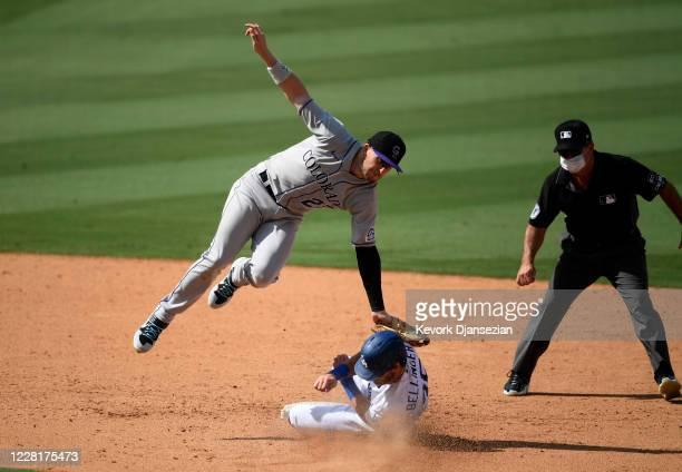 Trevor Story of the Colorado Rockies tags out Cody Bellinger of the Los Angeles Dodgers at second base during a steal attempt on a throw after a...