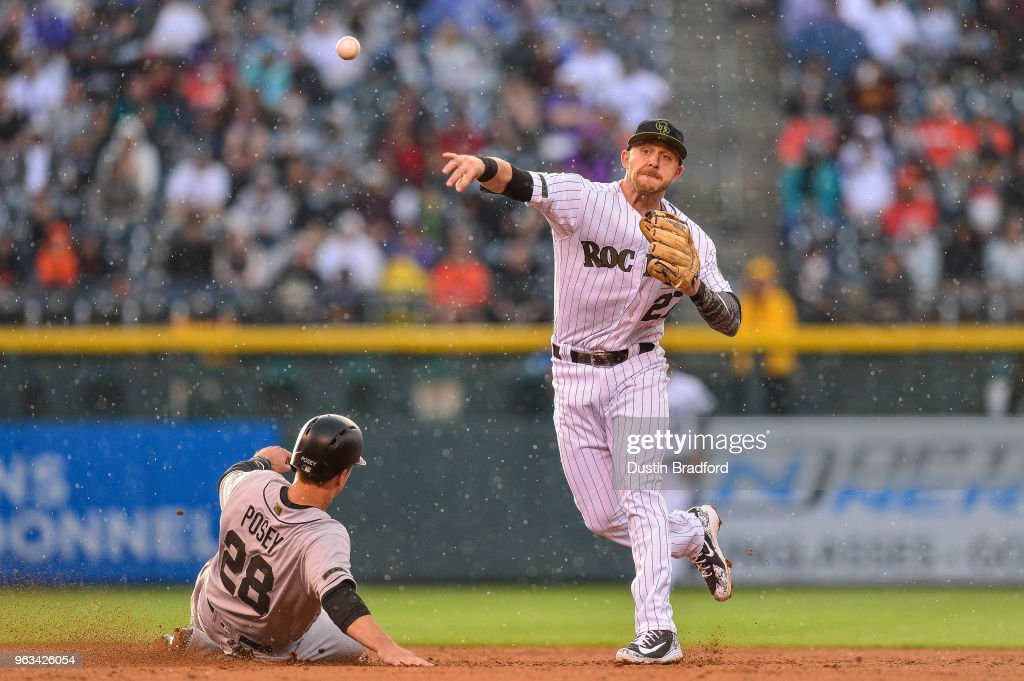 Trevor Story #27 of the Colorado Rockies throws past Buster Posey #28 of the San Francisco Giants to complete a third inning double play during a game\ at Coors Field on May 28, 2018 in Denver, Colorado.