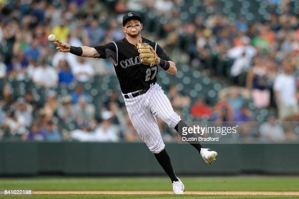 Trevor Story of the Colorado Rockies throws to first base for an out while blowing a bubble gum bubble in the sixth inning of a game against the...