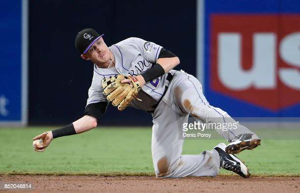 Trevor Story of the Colorado Rockies throws to second base to get the force out after making a diving stop on a ball hit by Erick Aybar of the San...