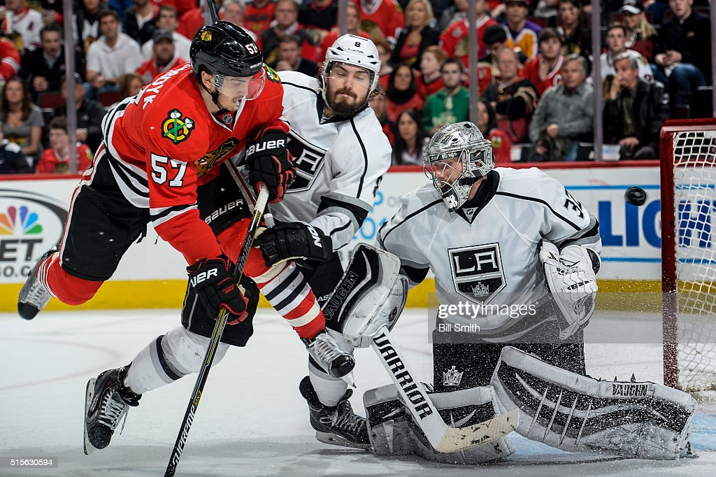 Trevor van Riemsdyk #57 of the Chicago Blackhawks and Drew Doughty #8 of the Los Angeles Kings get physical as the puck flys past goalie Jonathan Quick #32 in the third period of the NHL game at the United Center on March 14, 2016 in Chicago, Illinois.