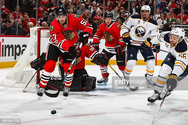 Trevor van Riemsdyk of the Chicago Blackhawks and Justin Bailey of the Buffalo Sabres chase the puck in the third period at the United Center on...
