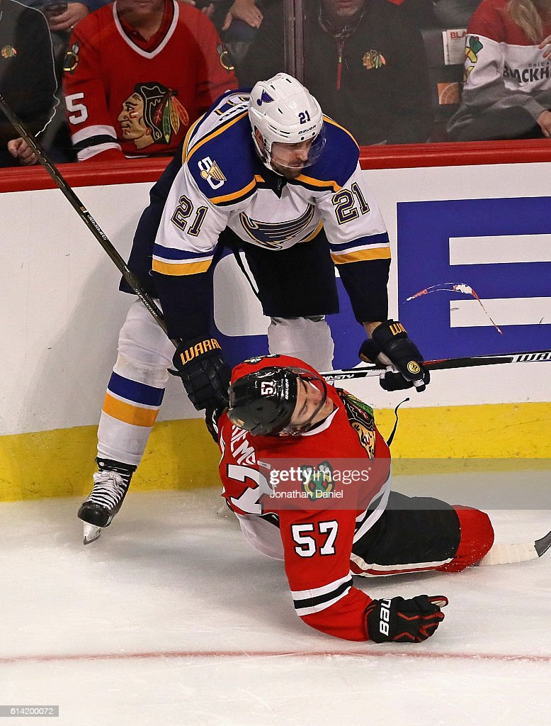 Trevor van Riemsdyk #57 of the Chicago Blackhawks hits the ice after a high stick from Patrik Berglund #21 of the St. Louis Blues during the season opening game at the United Center on October 12, 2016 in Chicago, Illinois.