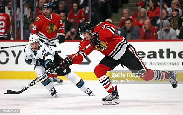 Trevor van Riemsdyk of the Chicago Blackhawks passes under pressure from Joonas Donskoi of the San Jose Sharks at the United Center on February 9...