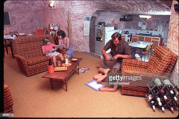 Trevor Weathermill sits with his son Brett while his wife Kate talks to their daughter Rebecca March 6 1989 in Coober Pedy Austrailia The family...