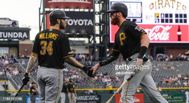 Trevor Williams of the Pittsburgh Pirates congratulates teammate Colin Moran on scoring against the Colorado Rockies in the first inning at Coors...