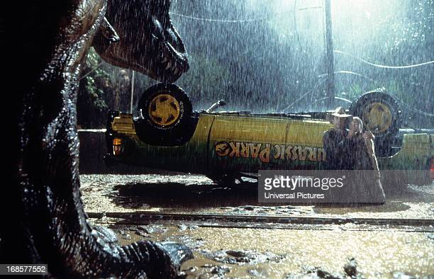 A trex approaches the flipped truck in a scene from the film 'Jurassic Park' 1993