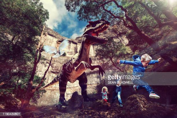 t-rex dinosaur chasing children - dinosaur stock pictures, royalty-free photos & images