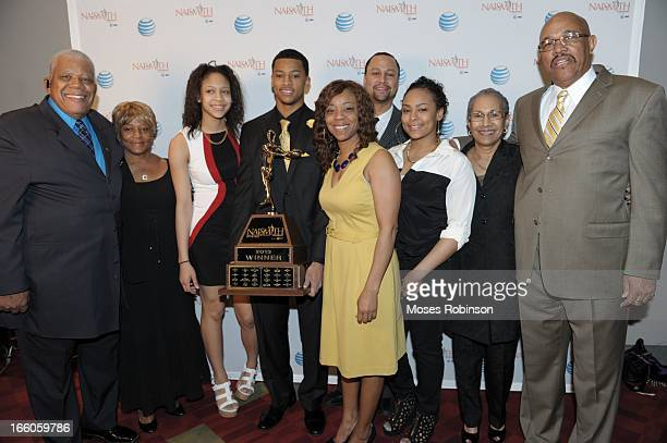 Trey Burke and his family pose with the 2013 Naismith Trophy at the NABC Guardians of the Game Awarding of the Naismith Trophy at Georgia World...
