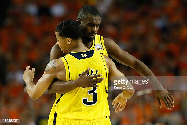 Trey Burke and Tim Hardaway Jr #10 of the Michigan Wolverines react in the second half against the Syracuse Orange during the 2013 NCAA Men's Final...