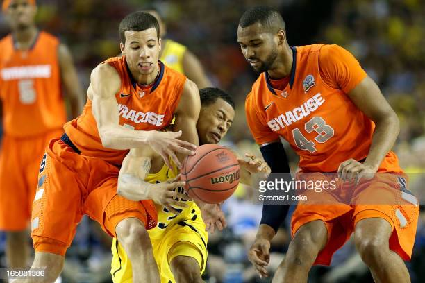 Trey Burke of the Michigan Wolverines attempts to control the ball in the first half against Michael CarterWilliams and James Southerland of the...