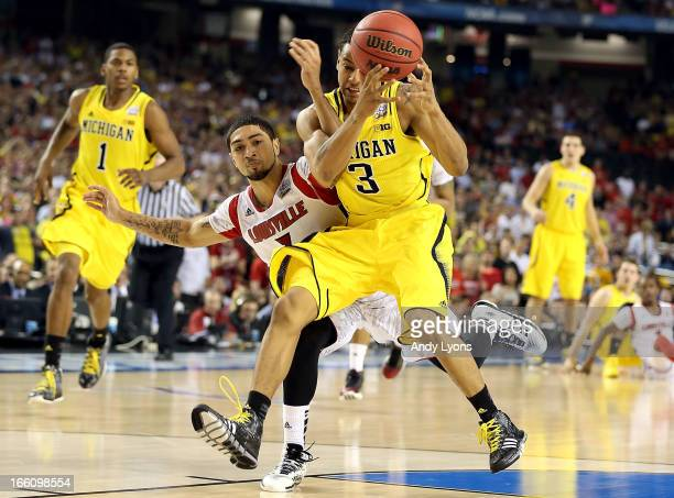 Trey Burke of the Michigan Wolverines attempts to control the ball in the second half against Peyton Siva of the Louisville Cardinals during the 2013...