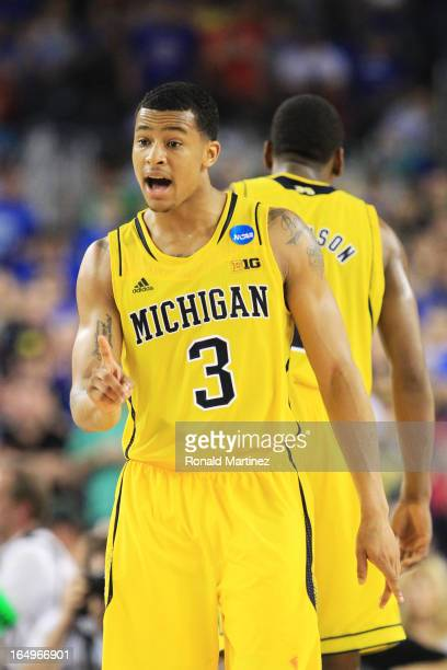 Trey Burke of the Michigan Wolverines celebrates during overtime against the Kansas Jayhawks during the South Regional Semifinal round of the 2013...