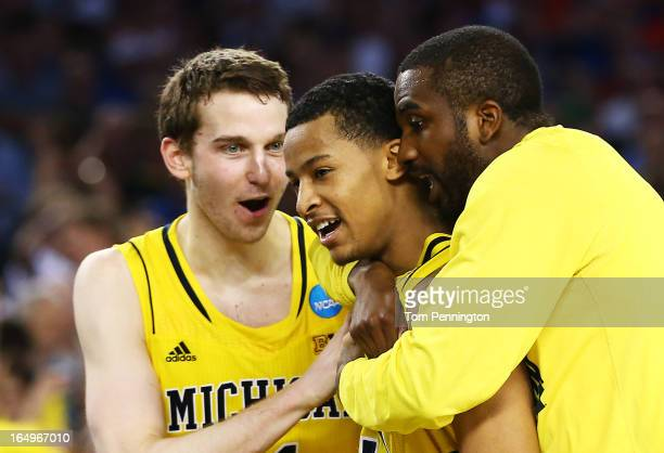 Trey Burke of the Michigan Wolverines celebrates their 87 to 85 win over the Kansas Jayhawks in overtime with teammates during the South Regional...