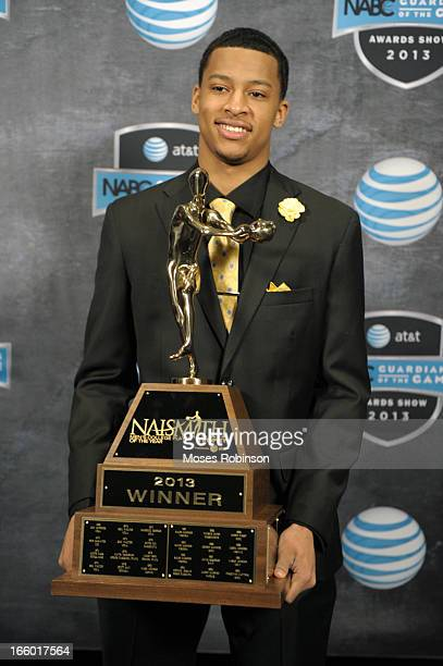 Trey Burke of the Michigan Wolverines poses with the 2013 Naismith Trophy at the NABC Guardians of the Game Awarding of the Naismith Trophy Presented...