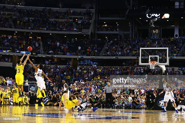 Trey Burke of the Michigan Wolverines shoots a game tying three pointer in the final seconds of the second half over Kevin Young of the Kansas...