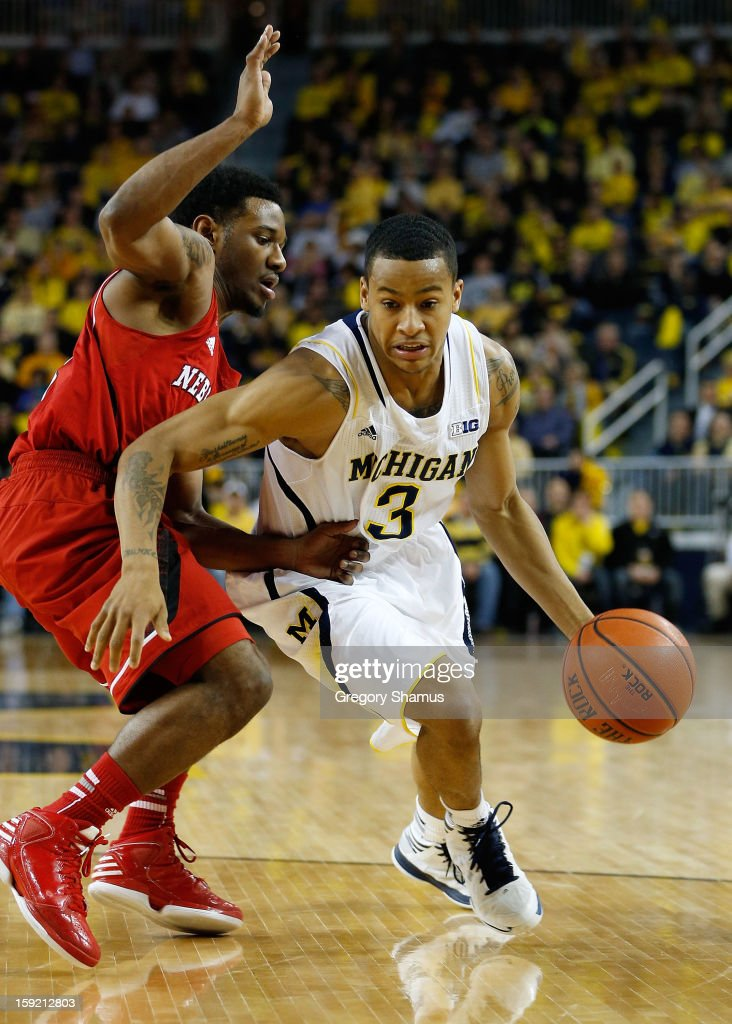 Trey Burke #3 of the Michigan Wolverines tries to drive around Benny Parker #3 of the Nebraska Cornhuskers at Crisler Center on January 9, 2013 in Ann Arbor, Michigan. Michigan won the game 62-47.
