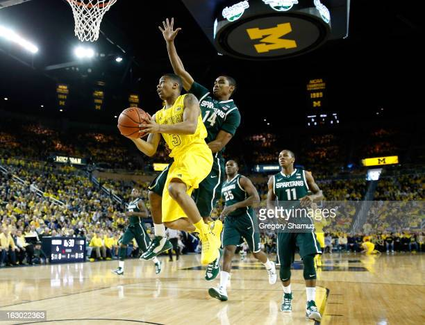 Trey Burke of the Michigan Wolverines tries to get a shot off in front of Gary Harris of the Michigan State Spartans during the first half at Crisler...