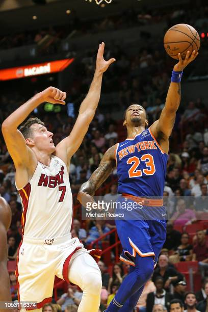 Trey Burke of the New York Knicks attempts a layup over Goran Dragic of the Miami Heat during the first half at American Airlines Arena on October 24...