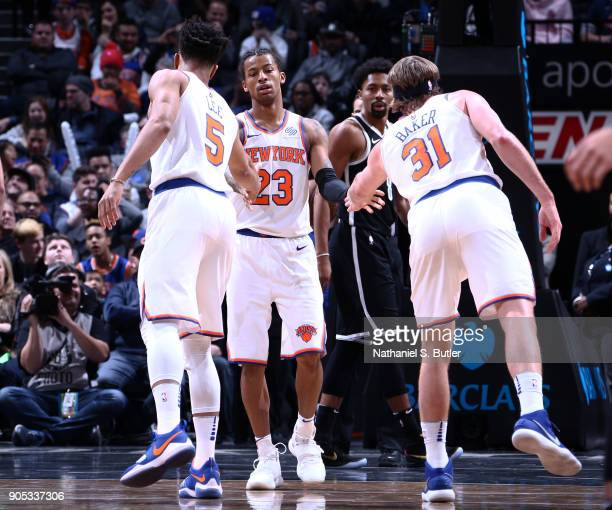 Trey Burke of the New York Knicks high fives his teammates during the game against the Brooklyn Nets on January 15 2018 at Barclays Center in...