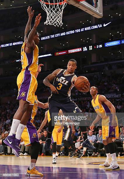 Trey Burke of the Utah Jazz looks to pass to the middle around Ed Davis of the Los Angeles Lakers in the first half during the NBA game at Staples...