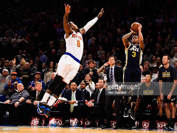 Trey Burke of the Utah Jazz shoots a gamewinning shot over JR Smith of the New York Knicks in the fourth quarter at Madison Square Garden on November...