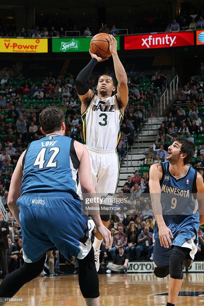Trey Burke #3 of the Utah Jazz shoots against Kevin Love #42 of the Minnesota Timberwolves at EnergySolutions Arena on February 22, 2014 in Salt Lake City, Utah.