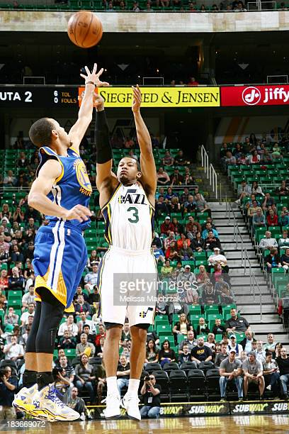 Trey Burke of the Utah Jazz shoots against Stephen Curry of the Golden State Warriors at EnergySolutions Arena on October 8 2013 in Salt Lake City...