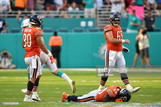 Trey Burton and Cody Whitehair look at Tarik Cohen of the Chicago Bears after a fumble against the Miami Dolphins at Hard Rock Stadium on October 14...